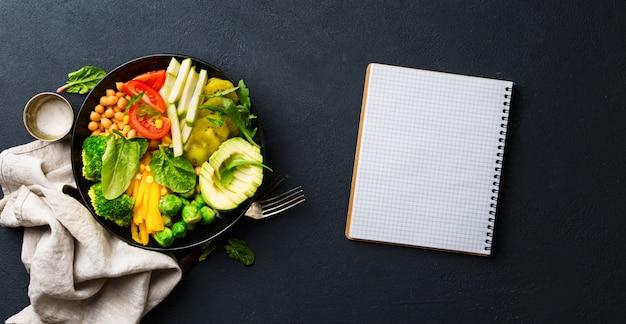Vegan gezond uitgebalanceerd dieet concept. vegetarische boeddha schaal met blanco notitieboekje. broccoli, paprika, tomaat, spinazie, rucola en avocado in plaat. bovenaanzicht
