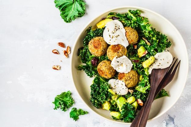 Vegan linzen gehaktballetjes met groene boerenkool salade, avocado en tahini dressing in een witte schotel, bovenaanzicht.