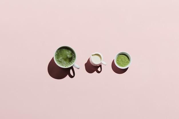 Vegan matcha latte met havermelk en ingrediënten op roze