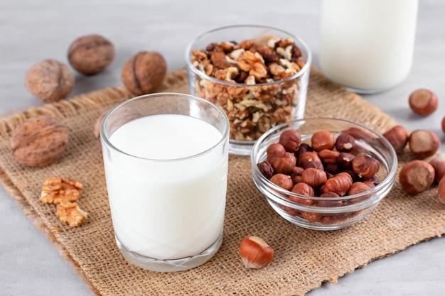 Vegan melk van noten in glazen pot met verschillende noten op witte houten achtergrond