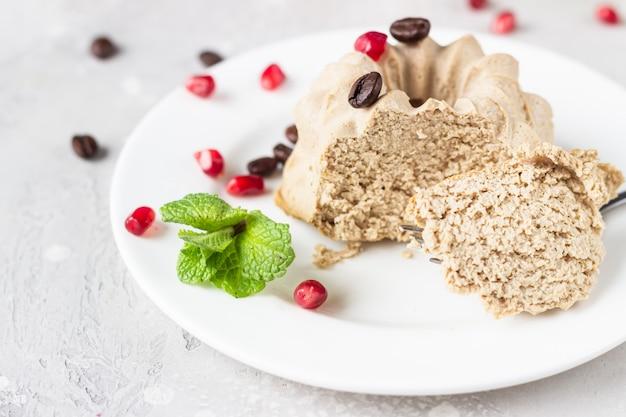 Vegan mini cheesecakes met koffie en banaan gegarneerd met koffiebonen, granaatappel en munt