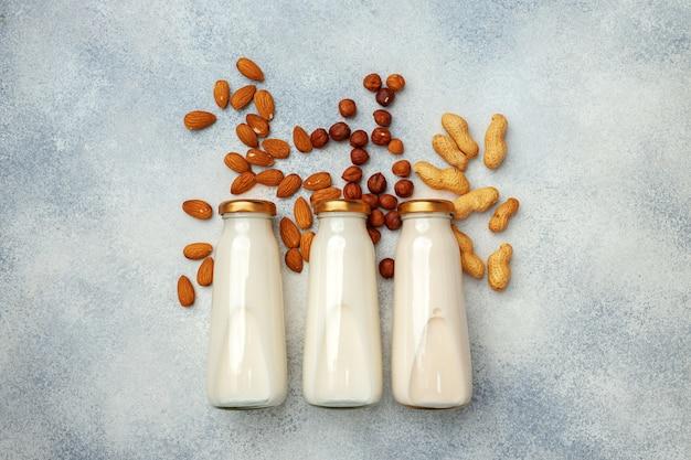 Vegan niet-zuivel notenmelk en hopen verschillende noten bovenaanzicht op houten bureau