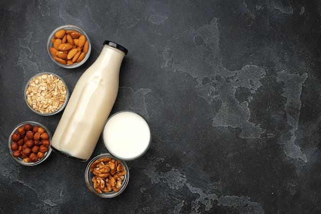 Vegan niet-zuivel notenmelk en hopen verschillende noten op houten bureau