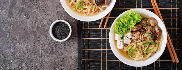 Vegan noedelsoep met tofu kaas, shiitake champignons en sla in witte kom. aziatisch eten. bovenaanzicht. plat liggen