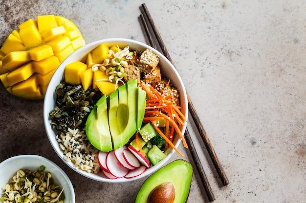 Vegan poke bowl met avocado, tofu, rijst, zeewier, wortelen en mango, bovenaanzicht. veganistisch eten concept.
