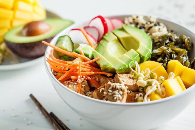 Vegan poke bowl met avocado, tofu, rijst, zeewier, wortels en mango. veganistisch eten concept.