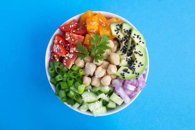 Vegan poke bowl met kikkererwten en groenten in de witte kom in het midden