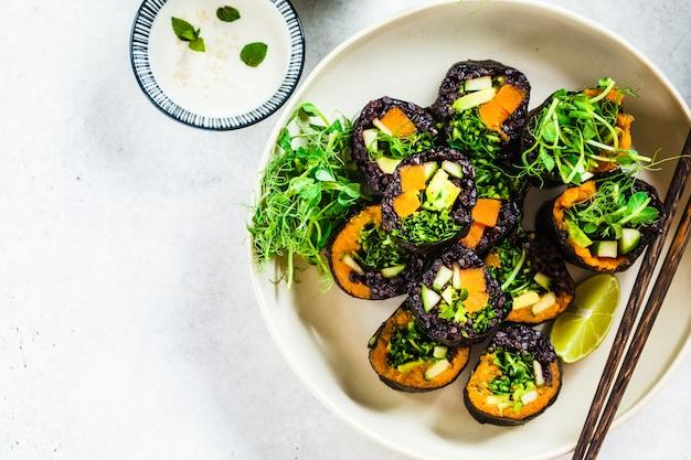 Vegan sushibroodjes met zwarte rijst, avocado en zoete aardappel op witte schotel