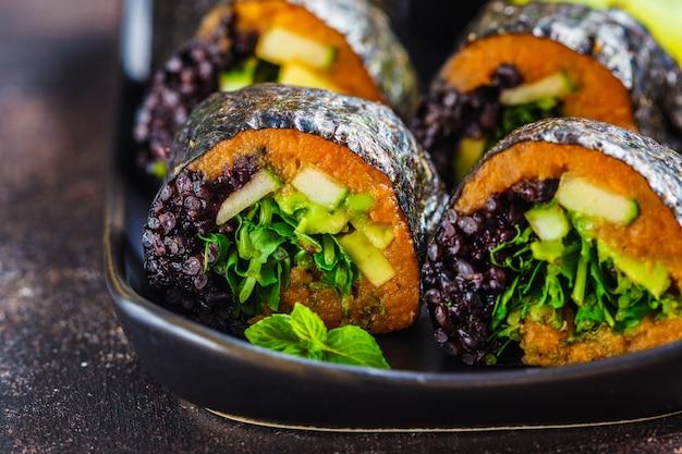 Vegan sushibroodjes met zwarte rijst, avocado en zoete aardappel op zwarte schotel