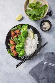 Vegan teryaki tempeh of tempe boeddha kom met rijst, gestoomde broccoli, spinazie en limoen op grijze achtergrond. gezond eten