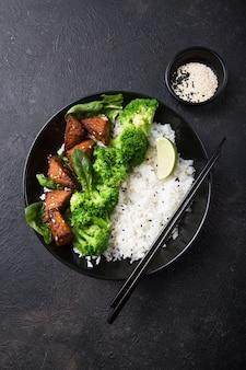 Vegan teryaki tempeh of tempe boeddha kom met rijst, gestoomde broccoli, spinazie en limoen op zwarte achtergrond. gezond eten