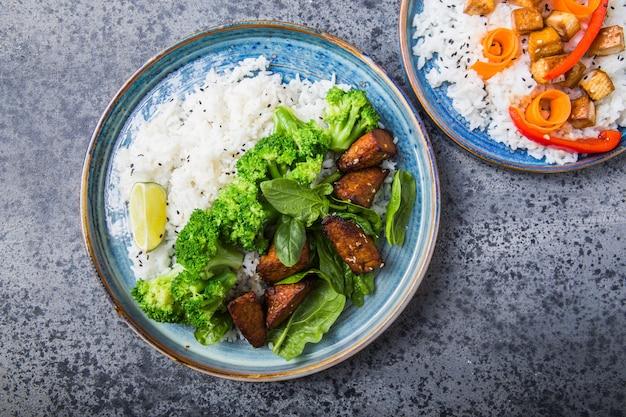 Vegan teryaki tempeh of tempe buddha kommen met rijst, gestoomde broccoli, spinazie en limoen op grijze achtergrond. gezond eten