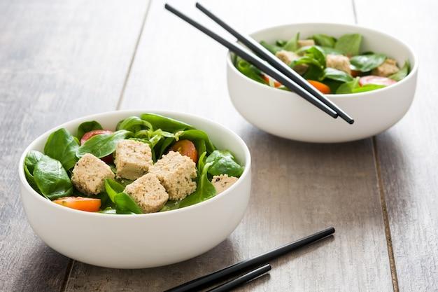Vegan tofu salade met tomaten en veldsla op een rustieke houten tafel