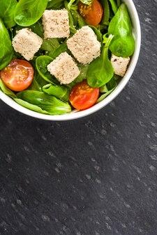 Vegan tofu salade met tomaten en veldsla op een zwarte leisteen