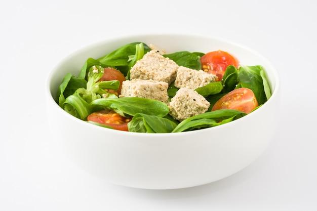 Vegan tofu salade met tomaten en veldsla op wit