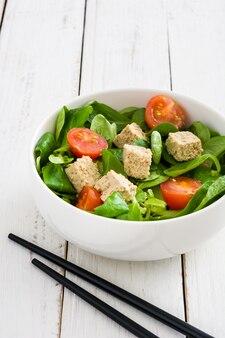 Vegan tofu salade met tomaten en veldsla op witte houten tafel