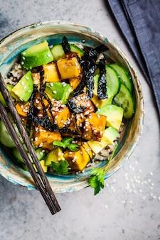 Vegan tofu zak met rijst, komkommer, avocado en nori op grijs