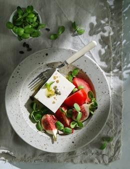 Vegan zomersalade met fetakaas, verse vijgen, tomaten, vijgen en groene bladeren. gezonde salade.