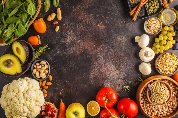 Veganist voedselingrediënten op een donkere achtergrond. groenten, fruit, granen, noten, bonen bovenaanzicht.