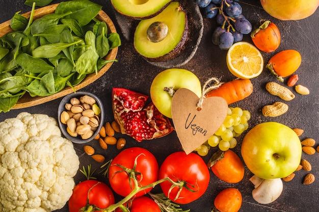 Veganist voedselingrediënten op een donkere achtergrond. groenten, fruit, granen, noten, bonen bovenaanzicht. Premium Foto