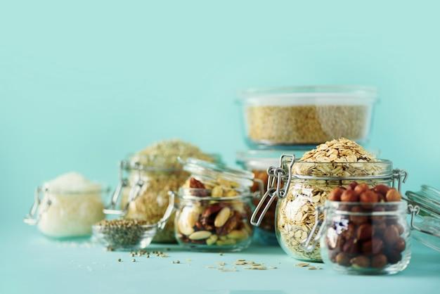 Veganistgezondheidsvoedsel over blauwe achtergrond met exemplaarruimte. noten, zaden, granen, korrels in glazen potten.
