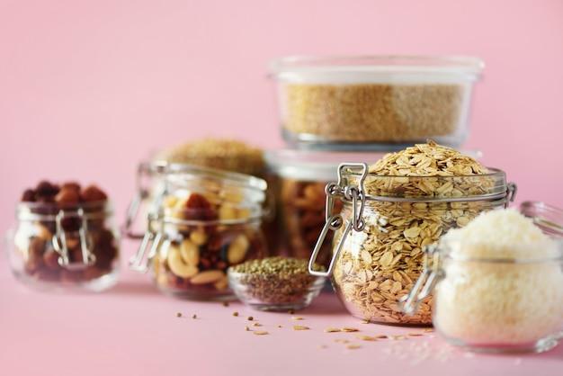 Veganistgezondheidsvoedsel over roze achtergrond met exemplaarruimte. noten, zaden, granen, korrels in glazen potten.
