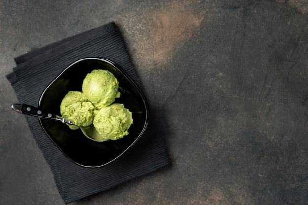 Veganistisch avocado-ijs in zwarte kom van bovenaf