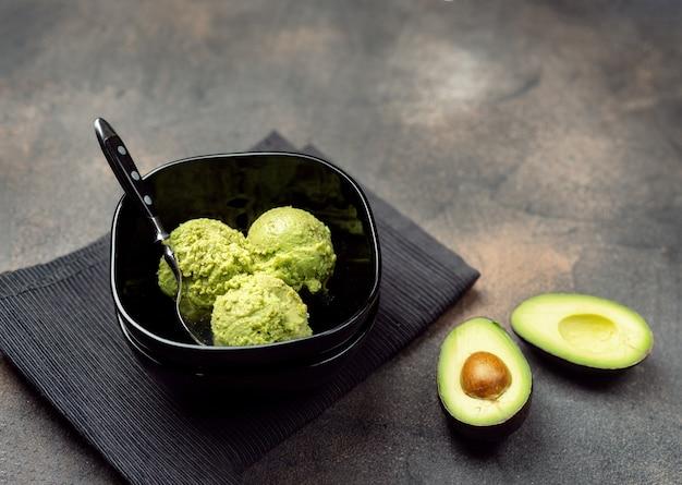 Veganistisch avocado-ijs in zwarte kom