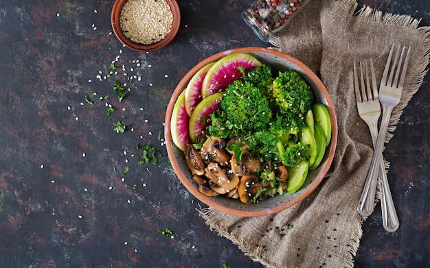 Veganistisch boeddha kom diner eten tafel. gezond eten. gezonde veganistische lunchkom. gegrilde champignons, broccoli, radijs salade. plat leggen. .