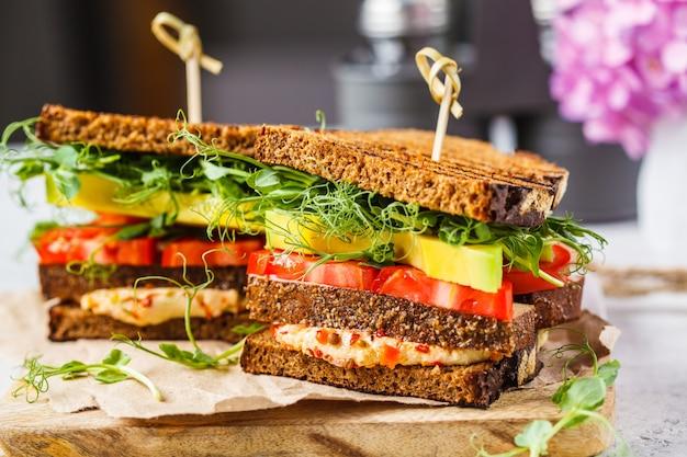 Veganistisch broodje met tofu, hummus, avocado, tomaat en spruitjes.