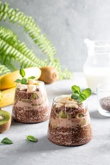 Veganistisch dessert, chia pudding met kiwi en banaan op grijze tafel. superfood