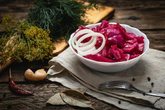 Veganistisch eten - ingelegde rode kool met uien op een houten oppervlak