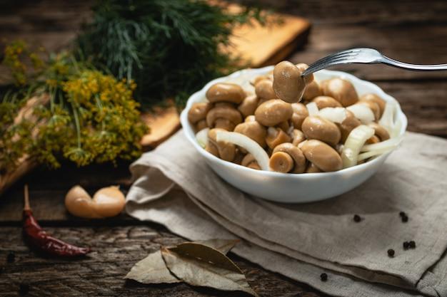 Veganistisch eten - ingemaakte champignons met plantaardige olie en uien op een houten oppervlak