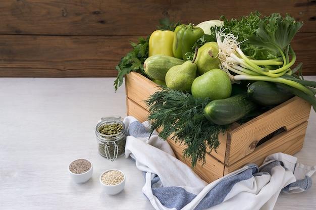 Veganistisch eten. verse groene hypoallergene groenten in houten kist en de zaden. selectieve aandacht