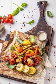 Veganistisch grillmenu, gegrilde groenten - courgette, paprika, cherrytomaten, maïs, wortelen en champignons geserveerd op een houten bord