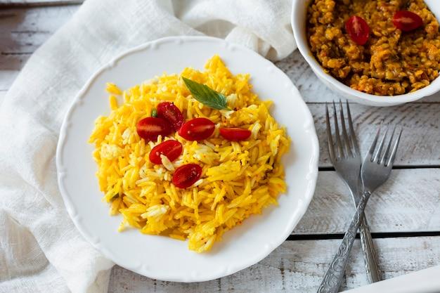 Veganistisch indisch voedsel met rijst en tomaten