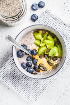 Veganistisch ontbijt. chia pudding met kiwi, bosbessen en pindakaas, bovenaanzicht.