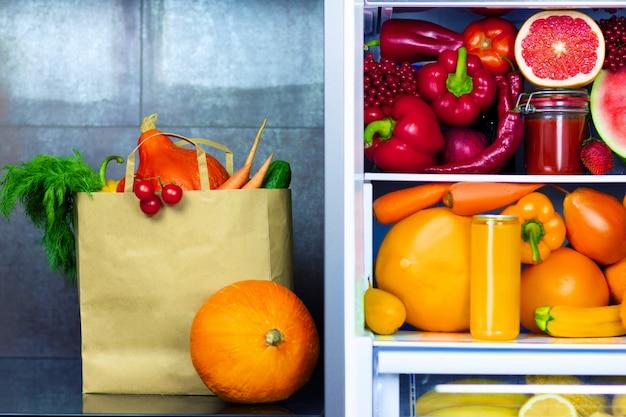 Veganistisch vegetarisch eco-papierpakket van groenten, fruit en groenten uit de markt op de keuken in de buurt van een koelkast met kleurrijke groenten, rauw sap en fruit: rode peper, sinaasappels, wortels, watermeloen, grapefruit