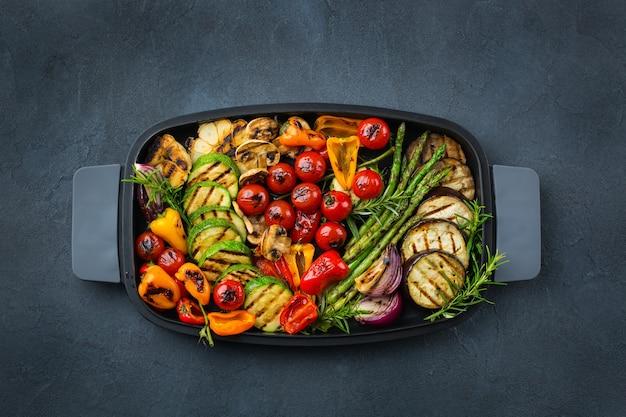 Veganistisch, vegetarisch, seizoensgebonden, zomers eetconcept. gegrilde groenten in een pan op een donkere zwarte tafel. bovenaanzicht plat lag achtergrond
