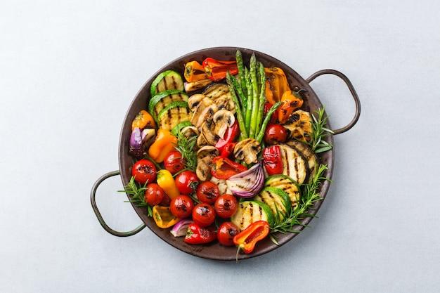 Veganistisch, vegetarisch, seizoensgebonden, zomers eetconcept. gegrilde groenten in een pan op een tafel. bovenaanzicht plat lag achtergrond