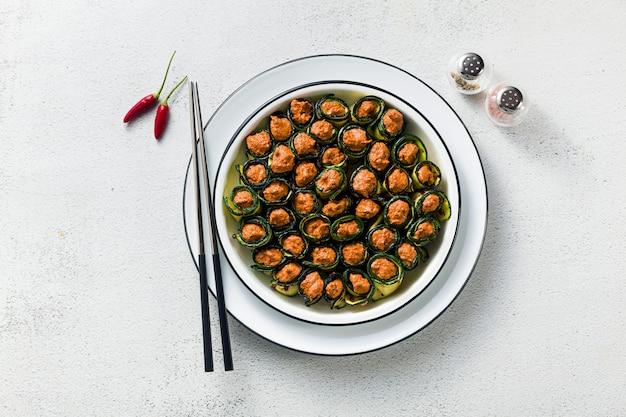 Veganistisch voorgerecht uit de georgische keuken. een zachte mix van gegrilde paprika en walnoten met pittige kruiden, gewikkeld in gegrilde courgette bladeren. gezonde keuken.