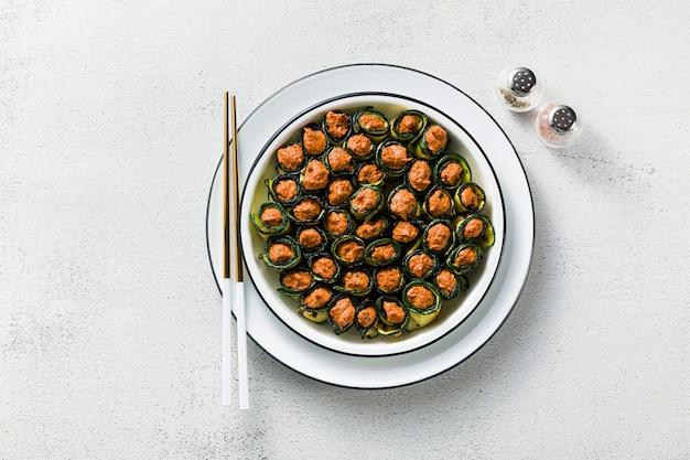 Veganistisch voorgerecht uit de georgische keuken. een zachte mix van gegrilde paprika en walnoten met pittige kruiden, gewikkeld in gegrilde courgette bladeren.