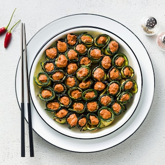 Veganistisch voorgerecht uit de georgische keuken. zacht mengsel van gegrilde paprika en walnoten met pittige kruiden, gewikkeld in gegrilde courgettebladeren. gezonde keuken. en eetstokjes