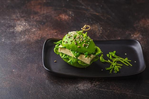 Veganistische avocado tofu burger op zwarte schotel. gezond detoxvoedsel, plantaardig voedselconcept.