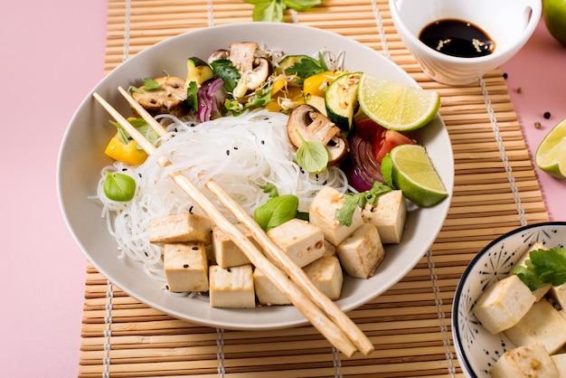 Veganistische aziatische lunch met rijstnoedels, tofu en groenten, traditioneel chinees of vietnamees eten met stokjes, bovenaanzicht