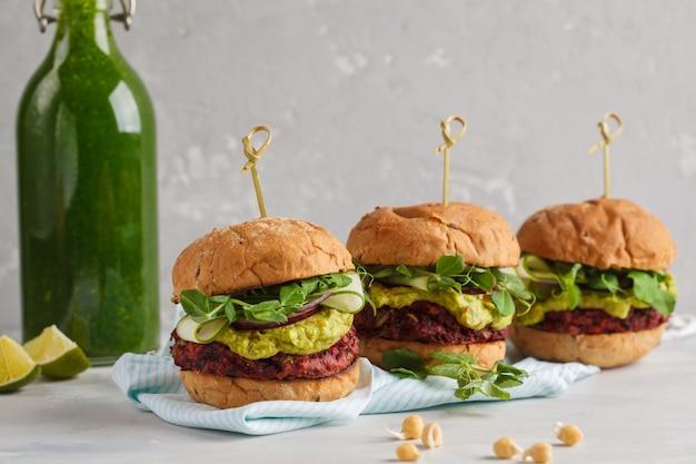 Veganistische bieten kikkererwtenburgers met groenten, guacamole en roggebroodje met groen sap. gezond veganistisch voedselconcept.