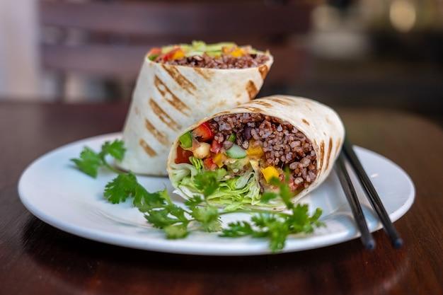 Veganistische burrito. gesneden rauwkost wrap met veganistische ingrediënten op een bord