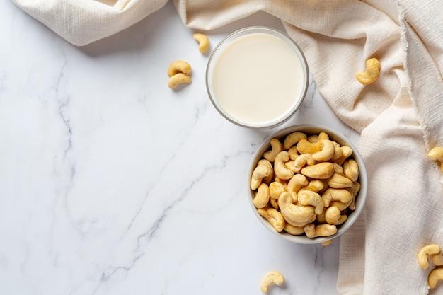 Veganistische cashewmelk in glas met cashewnoten op marmeren achtergrond
