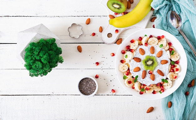 Veganistische chiazaadpudding met amandelmelk met banaan en kiwi. detox en gezond superfoods ontbijtkomconcept. bovenaanzicht, platliggend.