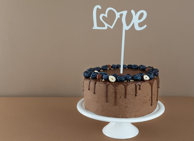Veganistische chocoladetaart met bosbessen, hazelnoten en het woord love op een bruine achtergrond